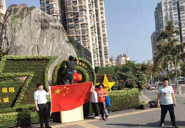 北京游客在植物绿雕国庆绿雕前举国旗合影